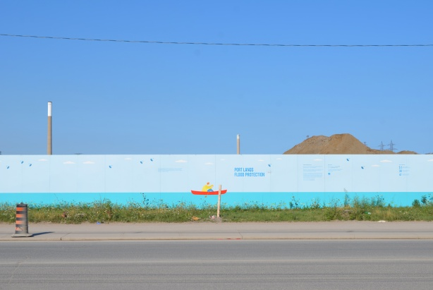 large painting on hoardings of a blue stripe on the bottom representing water of Lake Ontario and a small red boat