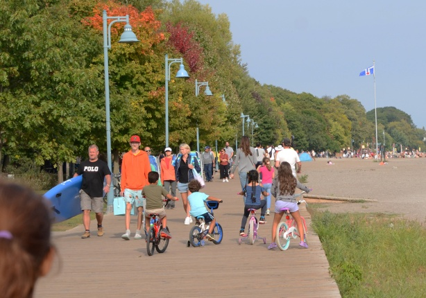 people walking on the boardwalk at Toronto waterfront, including four kids on their bikes, four aside, blocking traffic