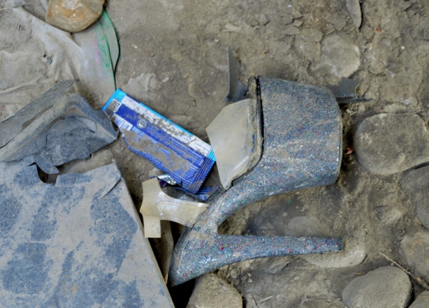 a high heel platform shoe in glittery silver and blue, very dirty, lying on its side in the dirt under the Gardiner, left behind garbage