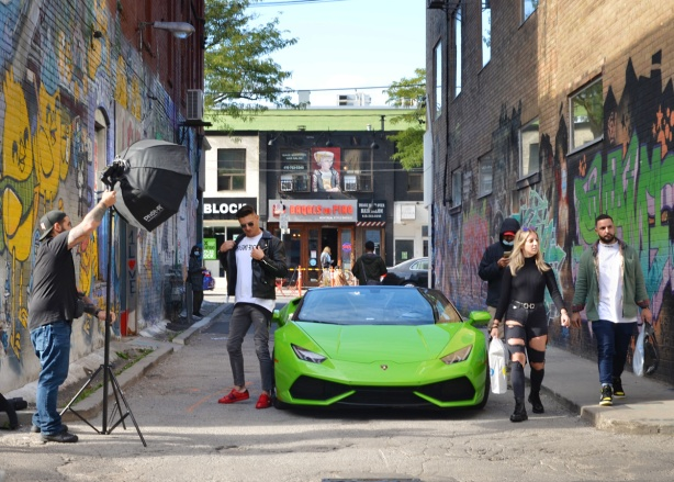 a young man in red shoes poses beside a green Ferrari parked in Graffiti Alley, being photographed, other people walking by including woman in ripped jeans