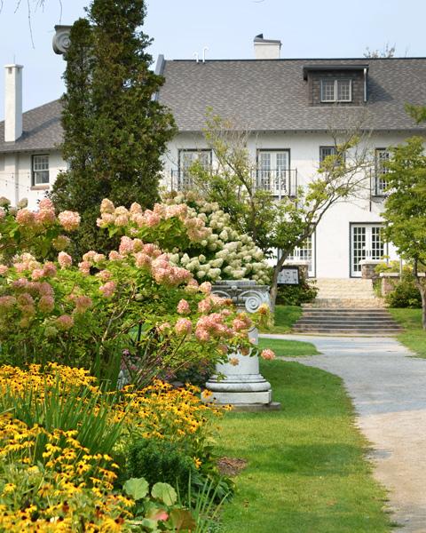 the old white house back of Guild Inn, with small stone columns in the garden along with trees and flowers