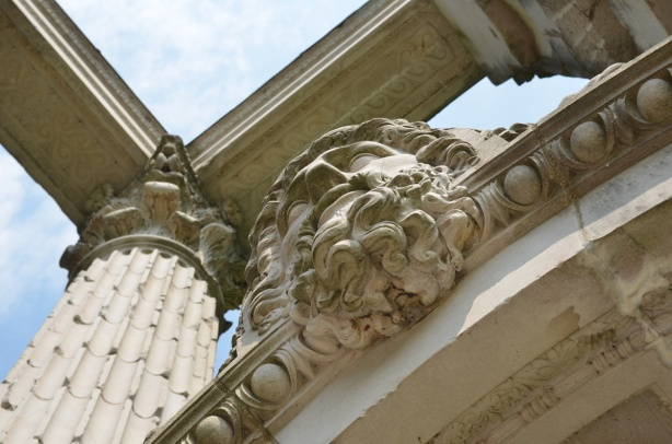 carved in stone, a head of an old man with curly hair and curly beard, with stone corinthian columns rising above him