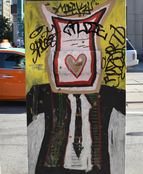 painting of a man on a traffic box, black suit and tie, white shirt, but brown paper bag over his face, with heart painted on it