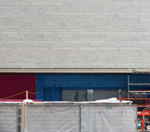 small section of wall in front of Holt Renfrew, grey cladding on top, part of pink and blue wall around the windows can be seen behind grey vinyl covered fence for construction