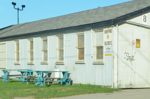 old building, one storey, with rusty metal bars on the windows, turquoise picnic tables outside,