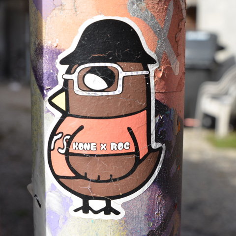 birdie ticker, orange shirt and black bowler hat, white glasses, with words on arm of t-shirt that says kone x roc