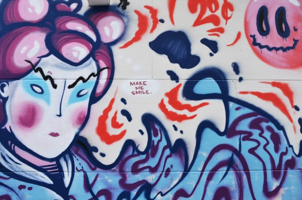 words, make me smile, and a Japanese looking face on a mural in an alley