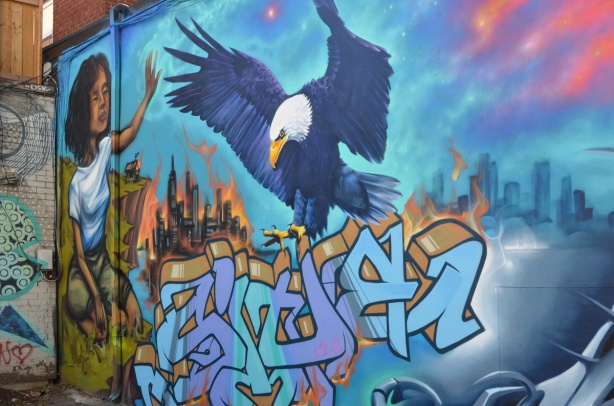 large mural on a wall, woman with a bald eagle, some text graffiti on it too