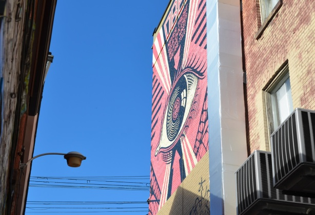 large mural of an eye by Obey, high on a wall near Graffiti Alley, faces QUeen Street West