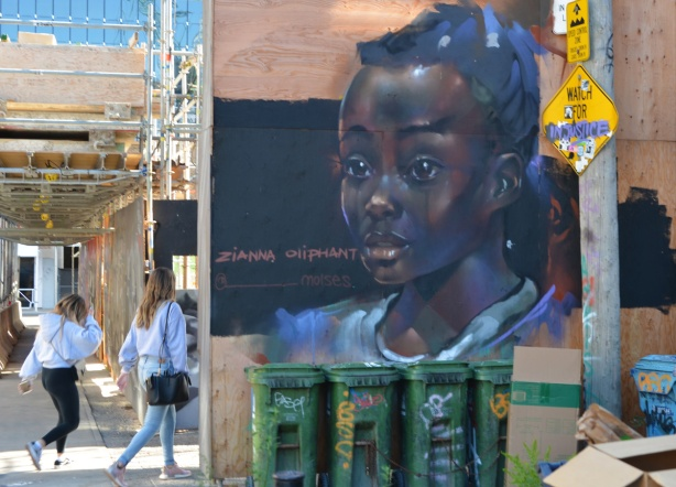 two women walk into an alley, past a mural featuring Zianna Oliphant, a black girl, garbage bins in front,