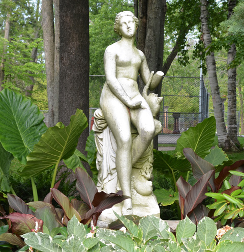 sculpture of a naked woman in a garden