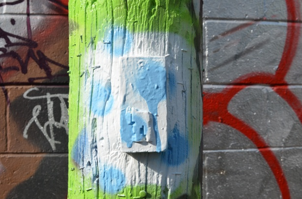 old stikman on a wood pole, only legs remaining, pole has been freshly covered with white and light blue spray paint