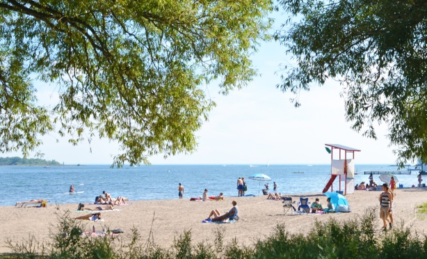 people on Cherry beach on a hot summer day, some walking, some lying or sitting on the sand
