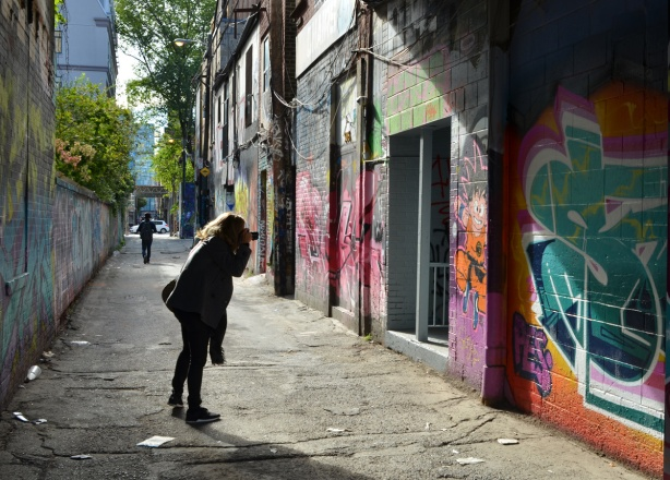 a woman takes a picture of street art in Graffiti Alley, late afternoon with low sun and long shadows