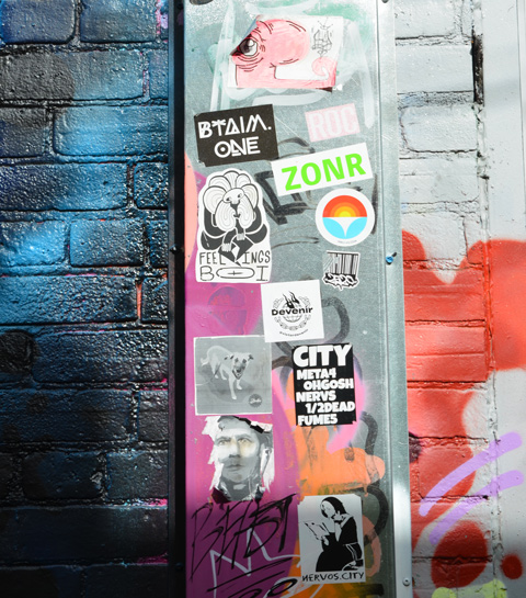 slaps and stickers on a pole with street art around it