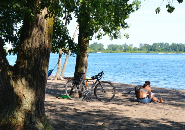 a woman sits on the sand at Cherry Beach, under a tree, with bike parked against the tree