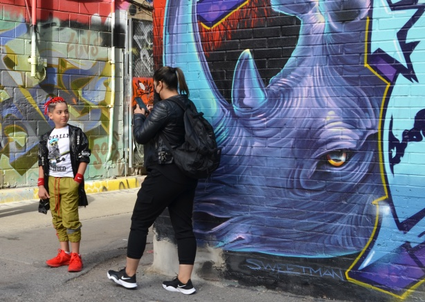 a mural of a purple rhinocerus by Nick Sweetman with a woman standing in front of it. She is taking a photo of a child in bright red shoes and red wool or ribbons braided into the hair