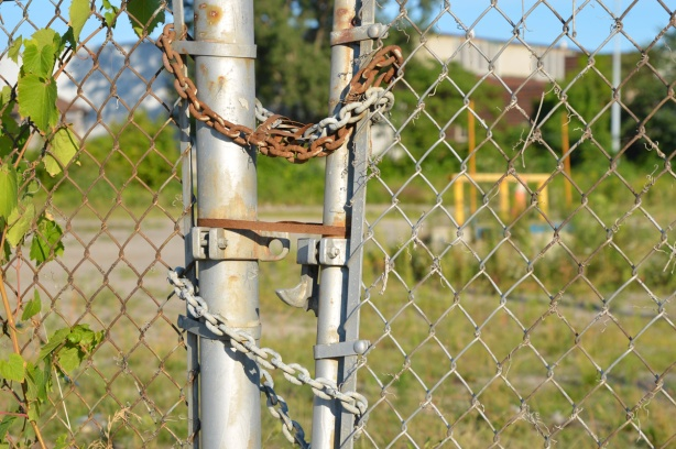 rusty chain holds a gate closed on chainlink fence, vacant lot behind