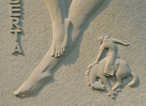detail of relief sculpture representing province of alberta in Guild inn garden, two bare feet, a cowboy riding a bucking broncho