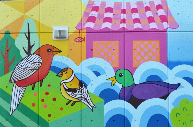 part of a mural by K J Bit Collective, mallard duck in water, goldfinch, and a cardinal in front of a pink building
