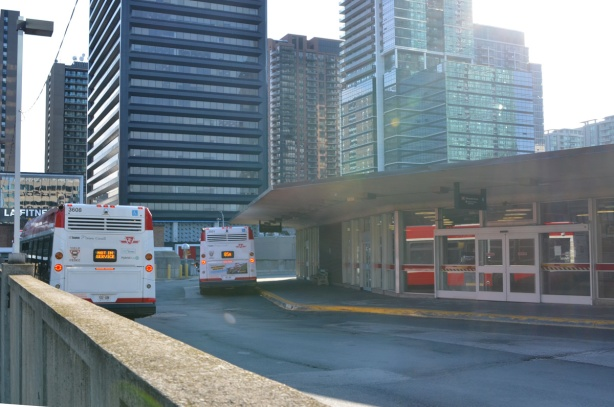 back of outside part of Shephard Subway station with a bus waiting by building, and an out of service bus parked towards the side, tall buildings of Yonge and Shephard area in the background