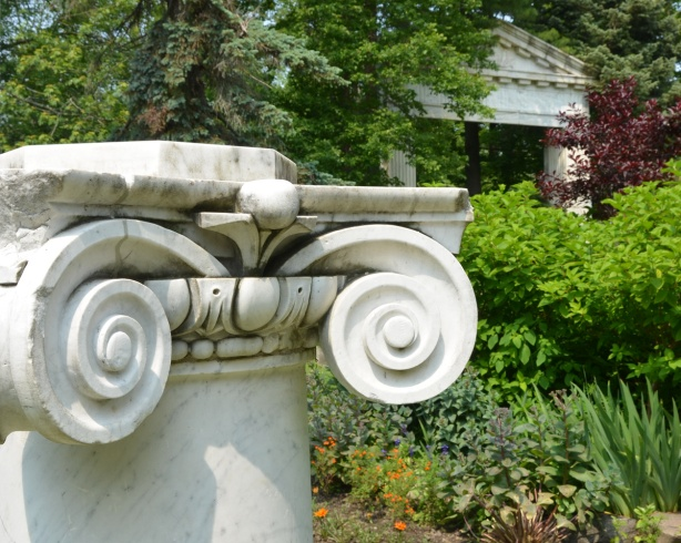 short white marble column in a garden