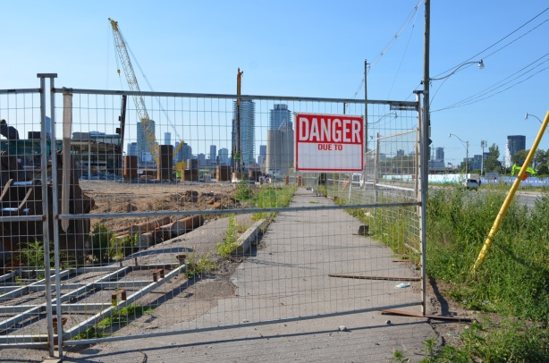 danger due to sign on a metal fence surrounding construction site which includes the sidewalk, Toronto skyline in the distance