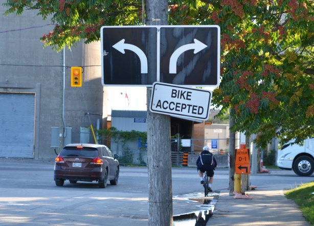 black and white arrow direction signs traffic signs, right lane turns right and left lane turns left. Also sign that says bike accepted.