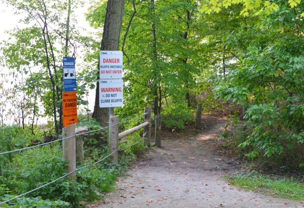 path through the woods with small fence on left. signs on left saying do not climb fence or cross over because of unstable ground, top of Scarborough bluffs, warning signs,
