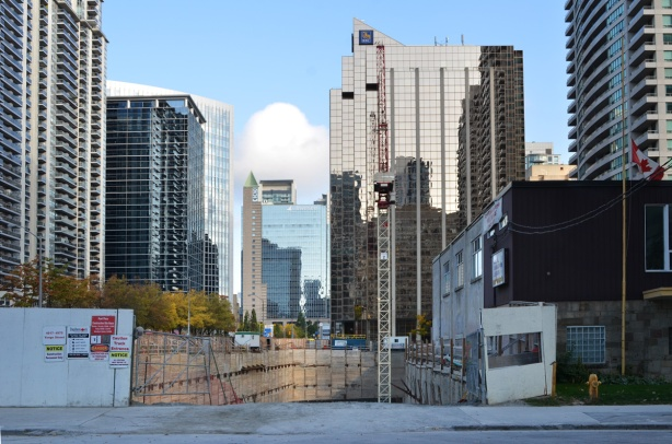 a large hole in the ground, construction at Yonge and Spring Garden, old Legion building in the right, tall North York buildings in the background
