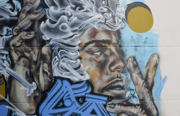 part of a mural of a black man with wavy white hair, blue text graffiti, and a yellow circle