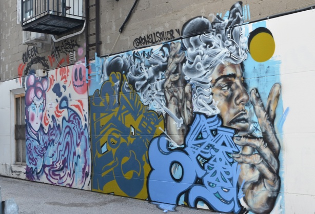 two murals on the side of a building in a small alley in North York