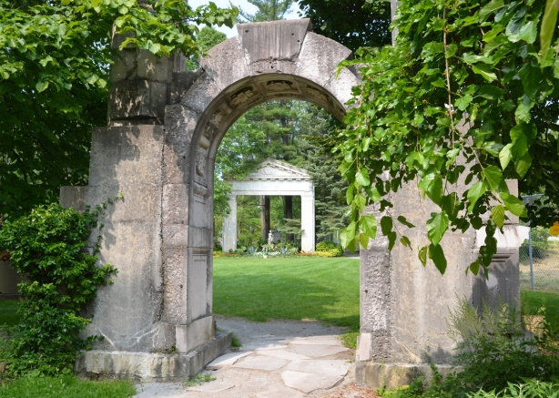 a statue under an arch as seen from an arch farther away, greenery, garden
