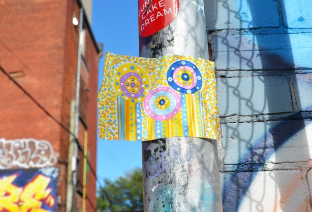 a sticker on a grey metal pole, yellow with an abstract design drawn in pinks, greens and blues with circles and vertical lines