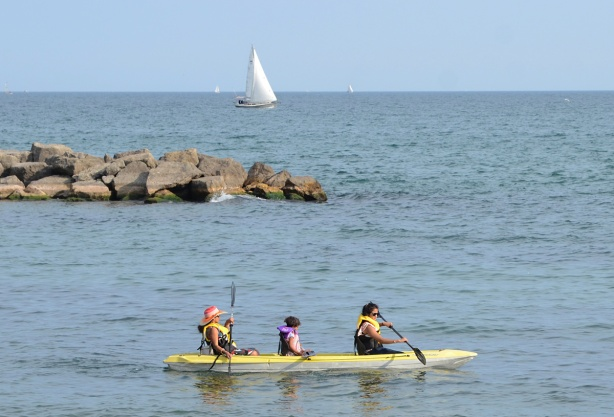 two women and a girl paddling in a yellow boat, a sailboat is in the background