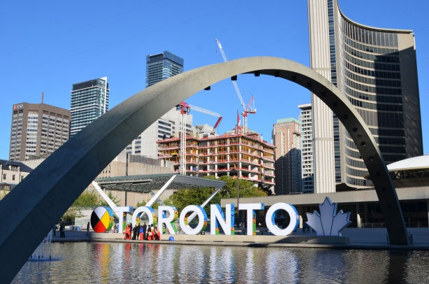 Nathan Phillips square with one arch prominent in the photo, reflecting pool, new Toronto sign, part of city hall, and construction of the new court house behind