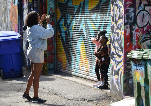 a mother takes a picture of two kids standing in front of a garage in Graffiti Alley