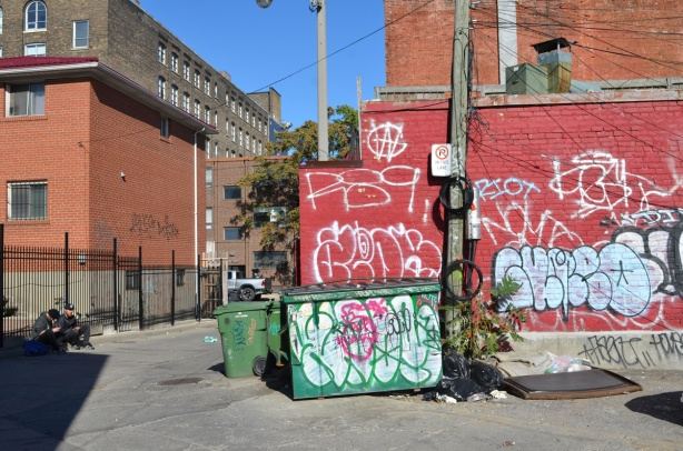 red brick wall with white tag graffiti, similar graffiti on green garbage bib two guys sitting on the curb on the other side of the lane