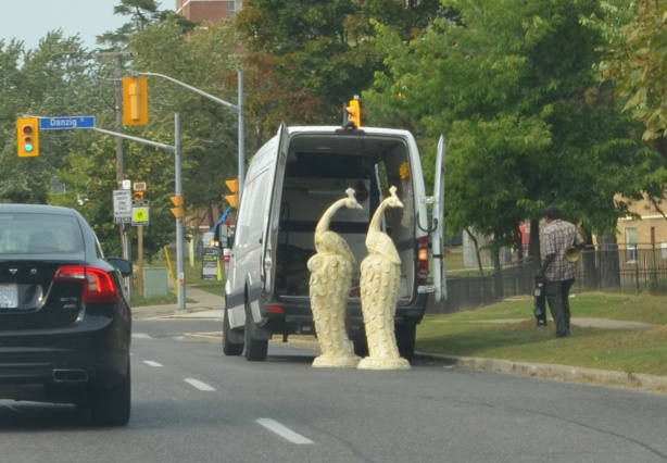 a van is unloading on the street, two large peacock sculptures, about 6 feet high in off-white, standing on the pavement
