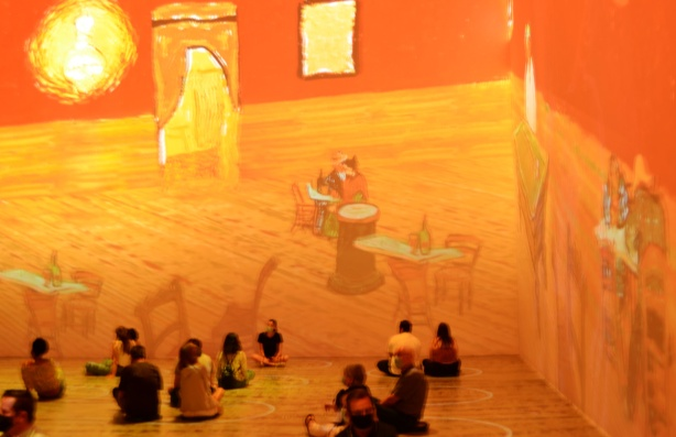 Vincent Van Gogh Immersive exhibit - people sitting on the floor with projections of images of inside of house with tables and chairs in orange and yellow tones