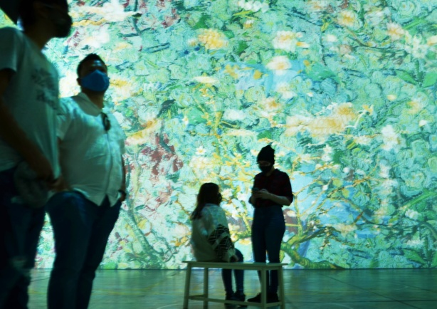 vincent Van Gogh Immersive Exhibit, 4 people, turquoise flowers, 2 men standing, one person sitting on a bench