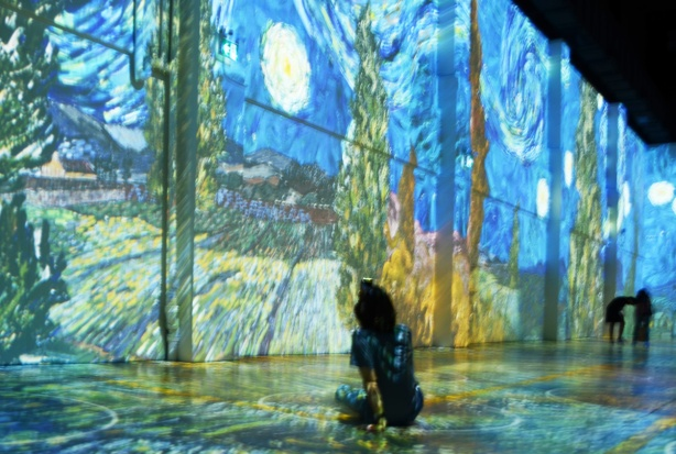 Vincent Van Gogh Immersive exhibit - person sitting on floor, taking aphoto with camera, starry starry night