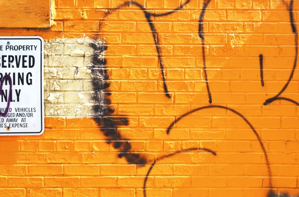 brick wall painted orange with graffiti on it