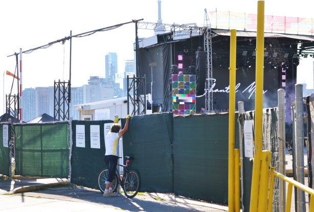 green covering on fence surrounding a temporary outdoor stage and theater. A man stands beside a bike, trying to look through gaps in the fence