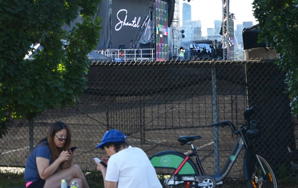 two people sitting on the ground looking at their phones in the foreground, fence between them and a singer rehearsing on a stage behind them