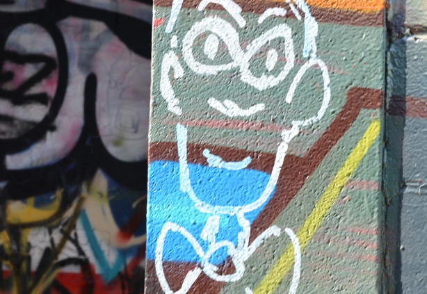 white line drawing of a man with a bowtie, head only, over coloured spray paint street art
