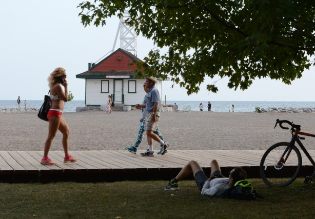 a man lies on the grass and watches people passing by on the boardwalk including a woman in a bathing suit and red shoes while talking on her phone, in front of Leuty Lifeguard station