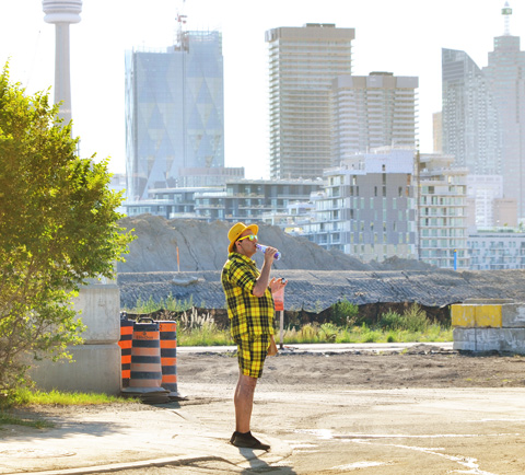 a man dressed in yellow plaid shorts and shirt stands on a corner