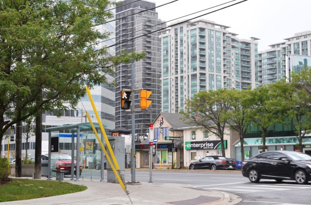 at the intersection of Yonge and Franklin in North York, older houses on Yonge street that are now businesses, with large new condo buildings behind
