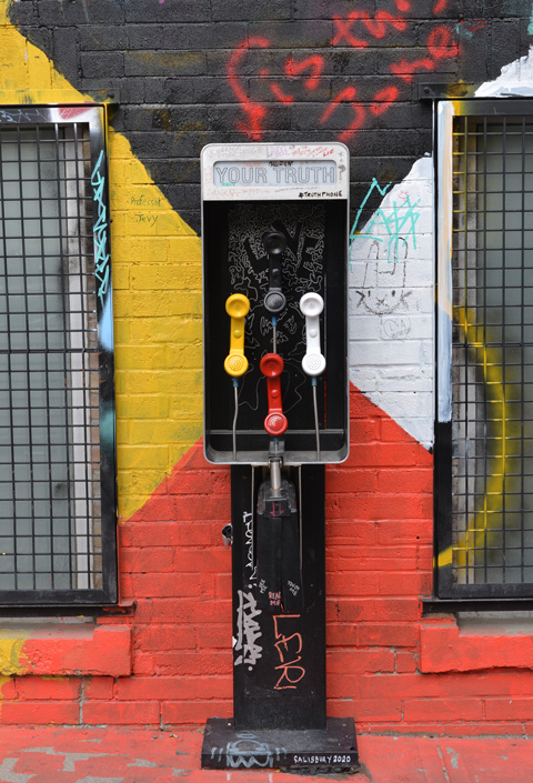phone booth with three ones, white, red, and yellow, with sign that says your truth
